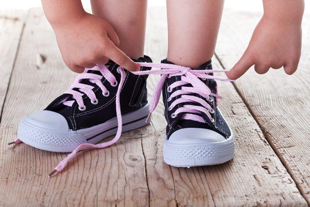 Niño anudando los zapatos.